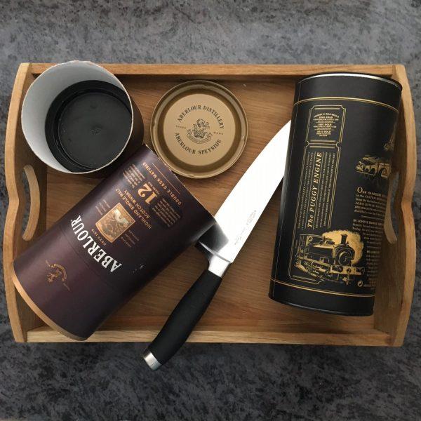 бутилки от уиски, поставени в дървена тава за сервиране, заедно с голпм нож